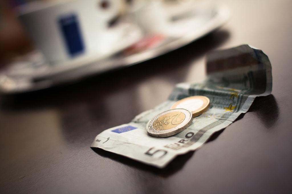 Geldschein und Münzen liegen auf einem Kaffeetisch
